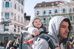 Father with child celebrate carnival at old center of Ljubljana,. Father with child son in carrier backpack at old center of Ljubljana, Slovenia. Kid looks at stock photos
