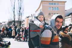 Father with child celebrate carnival at old center of Ljubljana,. Father with child son in carrier backpack at old center of Ljubljana, Slovenia. Kid looks at Stock Photography