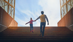 Father and child climb upstairs. Cute girl pulls her dad hand stock photography