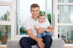 Father and child on couch. Portrait of smiling young father with child sitting on couch Royalty Free Stock Photo