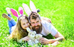 Father and child with cute bunny ears lying at meadow. Family feast concept. Dad and girl play in spring garden on sunny. Day. Man with beard and cute child lay royalty free stock photos