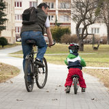 Father and child cycling. Father and a small child with his first bicycle cycling on a path in a city Stock Images