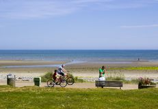 A father and child cycling along the new promenade at Newcastle County Down in Northern ireland on a bright and warm sunny day royalty free stock photography