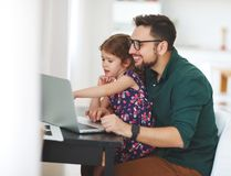 Father and  daughter working at a computer at home Royalty Free Stock Image