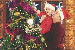 Father and child decorating fir tree at home. Image of young father with his son decorating a fir tree while celebrating Christmas tree at home stock image