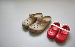 Father and child footwear. An adult and child rubber saddles on the ground royalty free stock photos