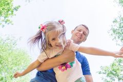 Father and child girl playing together. Father`s day concept. Dad is holding his daughter in his arms stock photography
