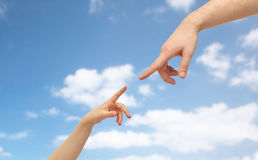 Father and child hands pointing fingers. Family and people concept - father and child hands pointing fingers to each other over blue sky and clouds background Stock Image