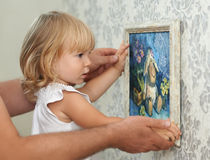 Father and child hanging picture on the empty wall Stock Photos