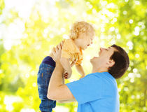Father child happy playing. Dad raise up smiling son over green stock photo