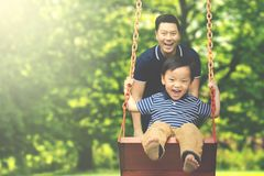 Father with child having fun in the park. Image of young father pushing his son on the swing while having fun in the park Stock Image