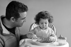 Father and child having meal together. Father (man age 35-45) takes care of his child (girl age 2-3) at meal time. Fatherhood, parenting and childhood concept Stock Photos