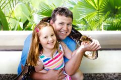Father and child hold and feed python snake at zoo. Father and child hold and feed huge python snake at day trip to zoo. Dad and kid watching wild animals in Royalty Free Stock Photo
