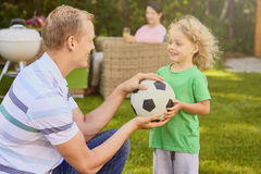 Father and child holding ball. Father and small child holding soccer ball Stock Images
