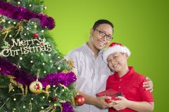 Father and child holding Christmas gift. Picture of happy father with his son holding Christmas gift while standing near a pine. Shot with green screen stock photos