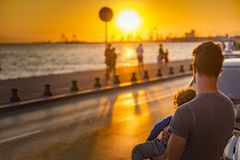 Father and child looking at sunset. AUGUST 2017, THESSALONIKI GREECE: Young father holding his child, enjoying a sunset view from the shore Royalty Free Stock Image