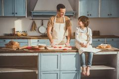 Father and child making cookies with pleasure. Dad rolling out dough for biscuits while his son sitting on kitchen table. They looking each other and smiling Stock Photography
