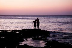 Father and Child Near on Body of Water during Sunset Stock Photos