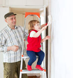 Father with child paints wall Royalty Free Stock Photography