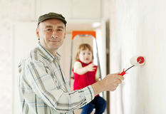 Father with child paints wall Stock Photography