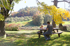 Father and Child Picnic under Trees at Apple Orchard Royalty Free Stock Photo