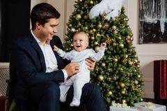 Father and child play Christmas. Dad holds a boy in his arms in white sliders. Business father. Father and child play Christmas. Dad holds a boy in his arms in Stock Photos