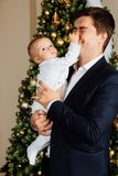 Father and child play Christmas. Dad holds a boy in his arms in white sliders. Business father. Father and child play Christmas. Dad holds a boy in his arms in Stock Image