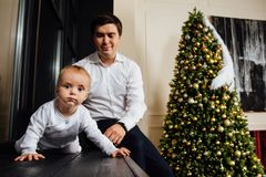 Father and child play Christmas. Dad holds a boy in his arms in white sliders. Business father. Father and child play Christmas. Dad holds a boy in his arms in Stock Photo