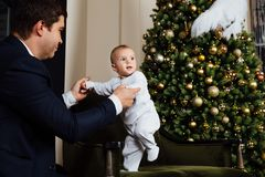 Father and child play Christmas. Dad holds a boy in his arms in white sliders. Business father. Father and child play Christmas. Dad holds a boy in his arms in Royalty Free Stock Image