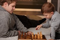 Father and child playing chess. Father and 4 years old child playing chess at home in a cold winter day Royalty Free Stock Image