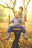 Father and child playing on a swing. Portrait of a cheerful young father and his son playing on a swing at the park, shot at autumn time Royalty Free Stock Photo