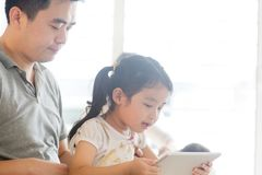 Father and child playing with tablet pc. Royalty Free Stock Images