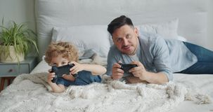 Father and child playing video game on bed at home pressing buttons on joystick. Father and little child are playing video game on bed at home pressing buttons stock video
