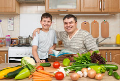 Father and child reading cooking book and choice dishes. Happy family having fun with fruits and vegetables in home kitchen interi Royalty Free Stock Images