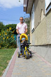 Father a child ride a tricycle royalty free stock photo