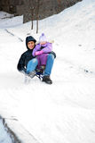Father and child riding on sled downhill. Royalty Free Stock Images