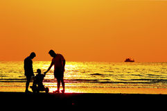 Father and  child by the sea shore, sunset Royalty Free Stock Photography