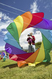 A father and child showing through the center of a rainbow colored kite Stock Photos