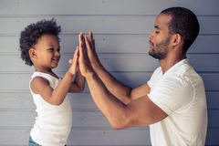 Father and child. Side view of handsome young Afro American father and his cute child touching hands and smiling, standing before gray wall Stock Images
