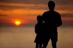 Father and child silouetted. Father and child silhouetted by sunset Royalty Free Stock Photo