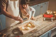 Man and boy taking photo of delicious food royalty free stock images