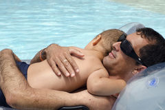 Father with child in swimming pool. Father holding and hugging a small child relaxing in a swimming pool on a inflatable mattress Royalty Free Stock Photo