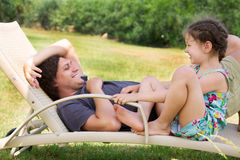 Father and child talking on a lounger. Royalty Free Stock Images