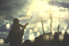 Father and child with three crucifixes. Image of father piggybacking his child while pointing at three crucifixes in the hill Royalty Free Stock Images