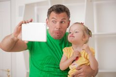 Father and child using electronic tablet at home Stock Image