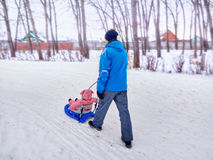 Father with child walk in the winter  the sledge on snow. Royalty Free Stock Photos