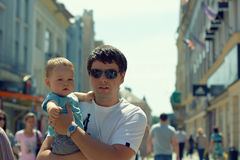 Father with child walking in the city. Father with child on hands walking through crowd outdoor in the city Royalty Free Stock Images