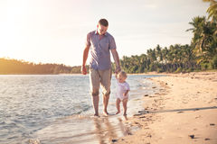 Father and child walking together on the beach coast during sunset with shining sea on background Stock Photos