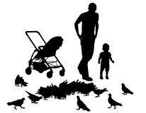 Father with child. Father walks with the baby in the stroller. They feed the pigeons Royalty Free Stock Photos