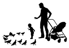 Father with child. Father walks with the baby in the stroller. They feed the pigeons Royalty Free Stock Photography